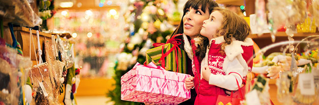 Mother and daughter holding wrapped presents and doing their holiday shopping